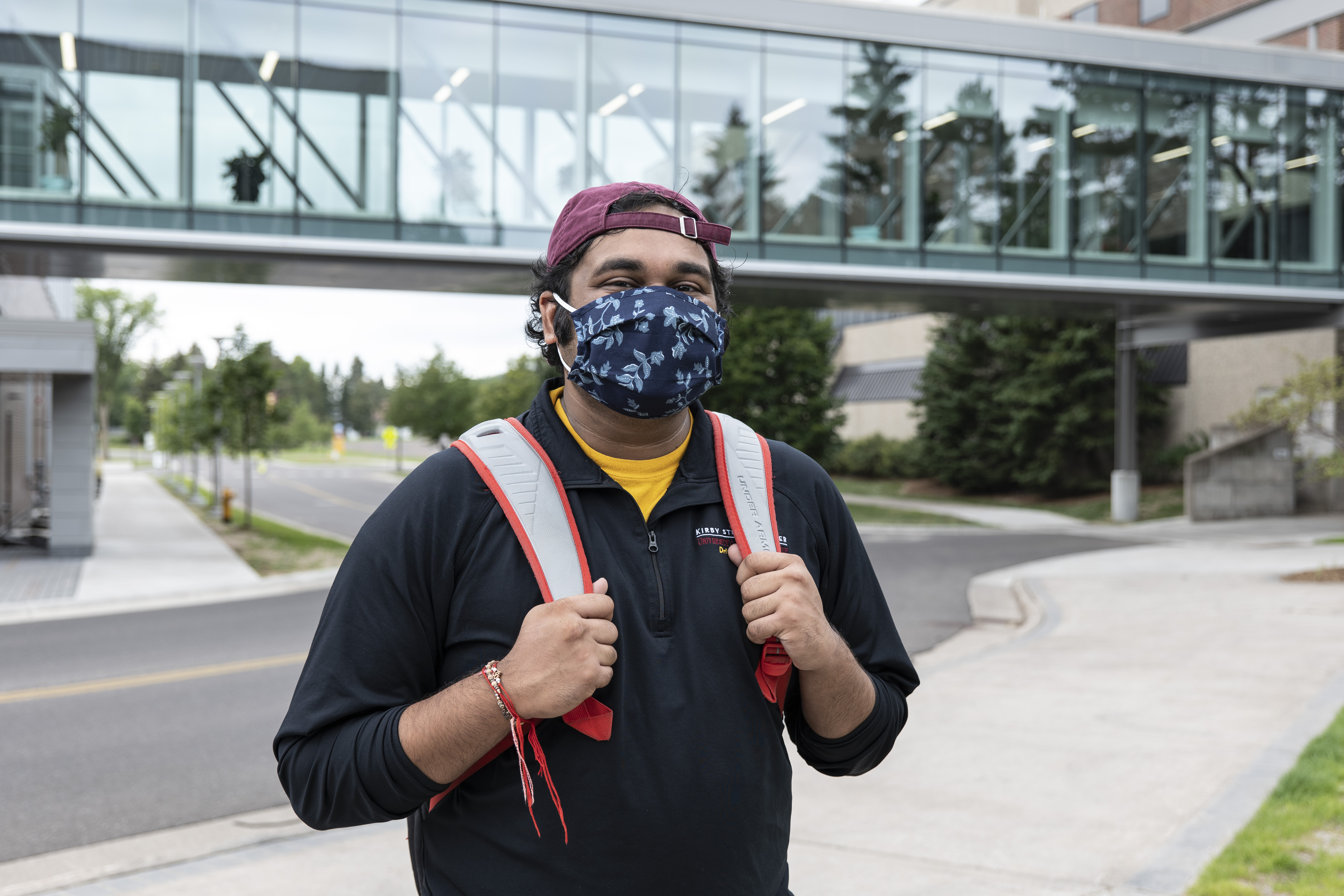 A young man outdoors on a college campus, wearing a mask